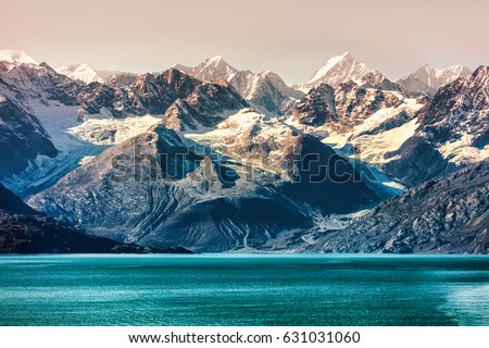 Glacier Bay National Park, Alaska, USA. Alaska cruise travel view of snow capped mountains at sunset. Amazing glacial landscape view from cruiseship vacation showing snowy mountain peaks.