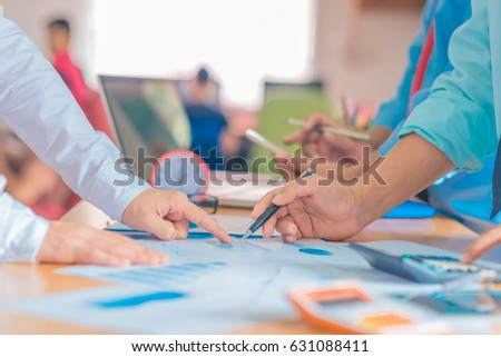 Business meeting, man's hands pointing on charts. Reflection light and flare. Concept image of data gathering and statistical working.