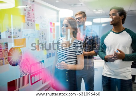 Creative business team reading sticky notes in office #631096460