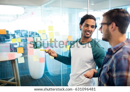 Creative business team looking at sticky notes and discussing in office #631096481