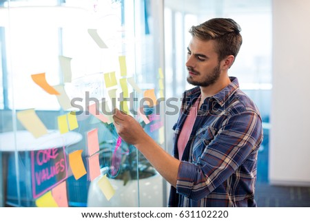 Close up of man reading sticky notes on the glass wall in office #631102220
