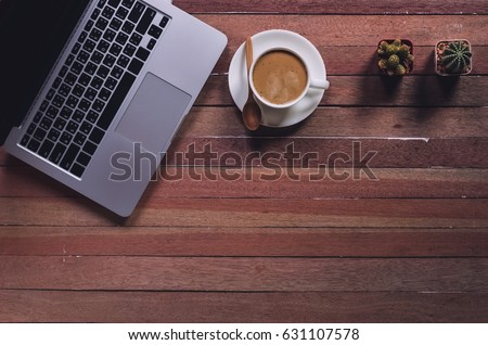 Office stuff and it gadgets display on top view business desk with copy space at text of picture. Creative table, modern project. Business mockup at empty laptop device on wood background. Dark tone. #631107578