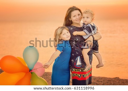 Young family standing in an embrace on the beach. Toned colored image.