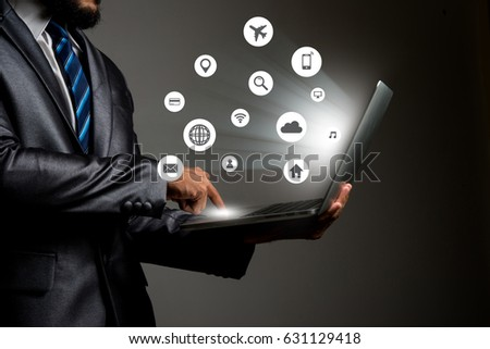 Businessman with multimedia icon interface on laptop conceptual image of social connection #631129418