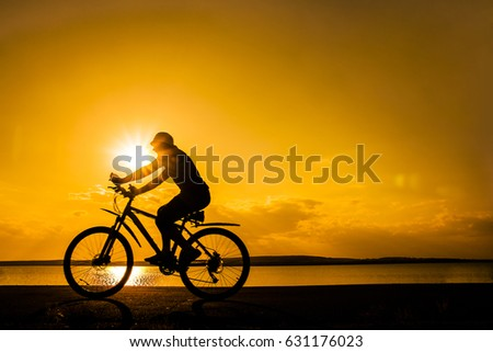 Image of sporty one tourist man walking along the shore with the bike against sunset sky with clouds and sun rays. alone woman Silhouette race with high speed #631176023