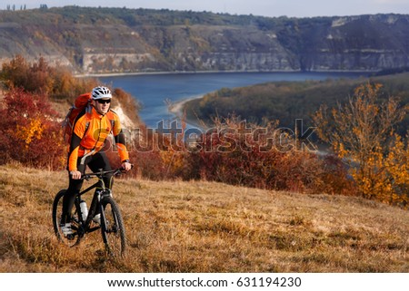 Young sporty man with red backpack riding a bicycle under the river with nature background. #631194230