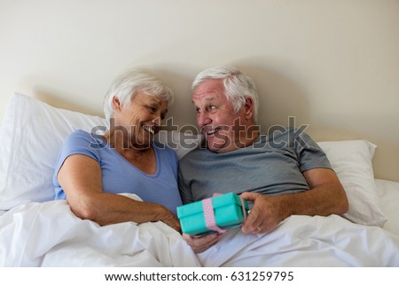 Senior man giving a surprise gift to woman in the bedroom at home #631259795