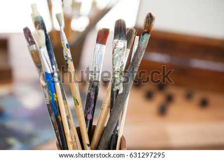 Set of paint brushes in a jar on wooden table #631297295