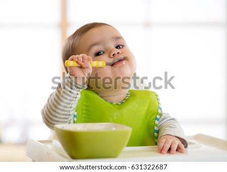 Happy infant baby boy spoon eats itself #631322687
