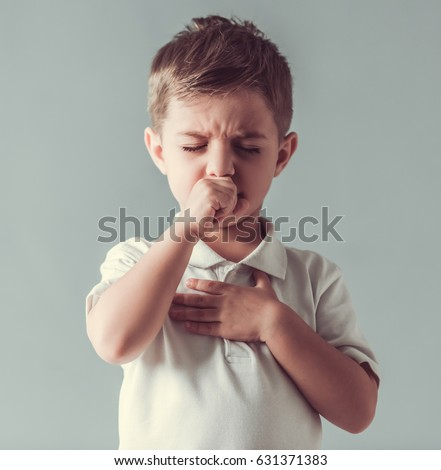 Cute little boy is coughing, on gray background Royalty-Free Stock Photo #631371383