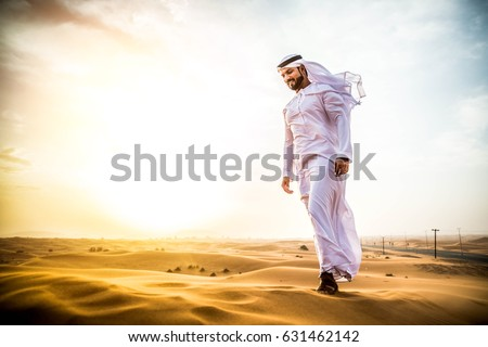 Arabian man walking  in the desert at sunrise #631462142