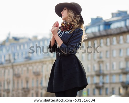 Young woman in stylish clothes against the background of the city, romantic portrait. Portrait of the charming blonde on the street.