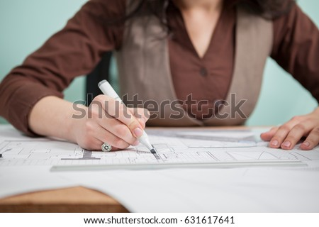 Architect woman at her table drawing on blueprints. Business and creativity. Architecture job #631617641
