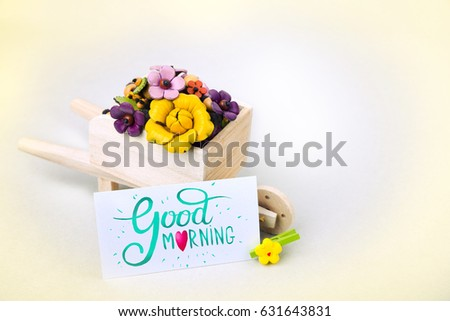 Morning surprise, wheelbarrow with flowers and a card. A colored inscription is a good morning!