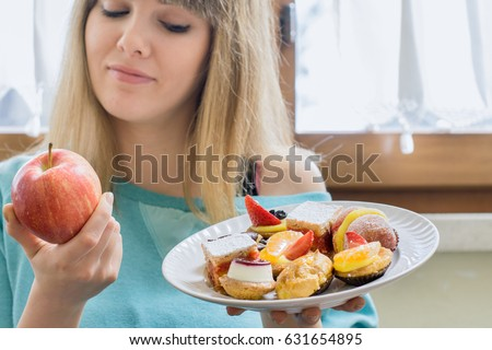 Diet. Woman Holding Sweets, unhealthy junk food and Apple. Concept of choosing Healthy Eating and Dieting for weight loss, nutrition no Health Risks through resisting bad eating habits.  #631654895