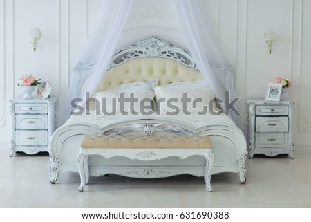 Luxury bedroom in light colors with golden furniture details. Big comfortable double royal bed in elegant classic interior #631690388