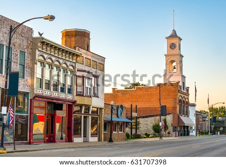 Traditional main street downtown of quaint rural USA small town in midwest America with storefronts and  clock tower Paxton Illinois America Royalty-Free Stock Photo #631707398