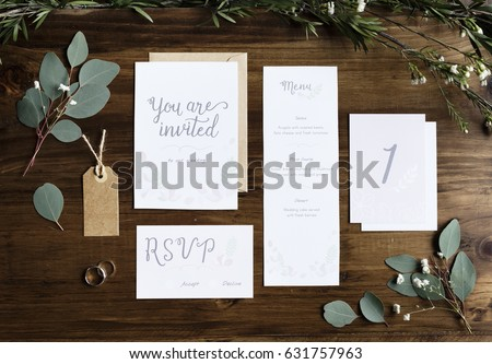 Wedding Invitation Cards Papers Laying on Table Decorate With Leaves #631757963