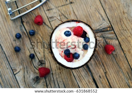 Ice cream in a coconut with berry syrup and fresh berries #631868552