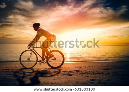 Silhouette of sportsman riding a bicycle on the beach. Colorful sunset cloudy sky in background. #631883180