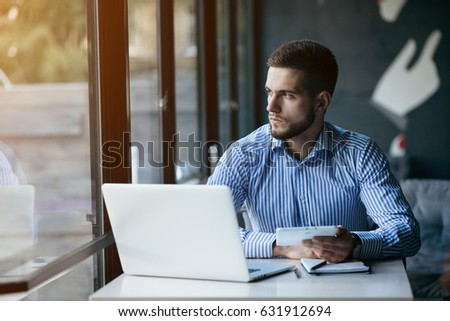Young man drawing template for the web site associated with digital marketing, current trends and tendencies of UX / UI design. Businessman who rules his company remotely, like a freelancer #631912694