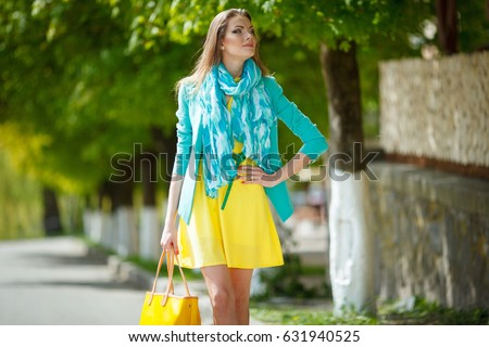 Beautiful brunette young woman wearing nice dress, yellow handbag, walking on the street. Fashion city photo. #631940525