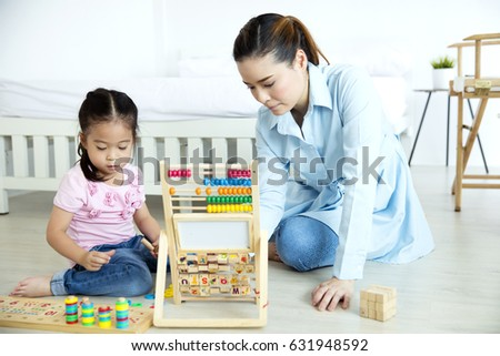 Asian mother and daughter playing wooden toys in the bedroom #631948592