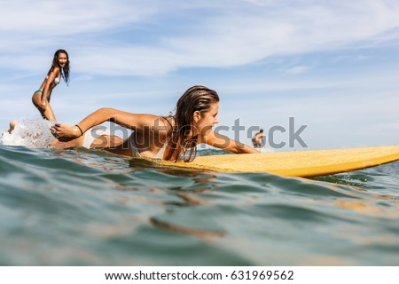 Two beautiful fit surfing girl on surf longboard surfboard board on sunrise or sunset in the ocean. Woman ride good wave while her friend paddle. Modern active sport lifestyle and summer vacation. #631969562