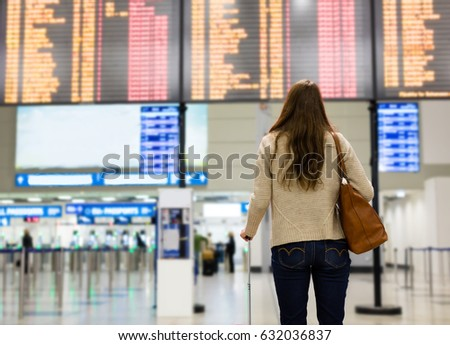 Young woman looking at the flight information board on the airport, checking her flight #632036837