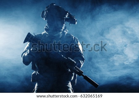 Army soldier in Combat Uniforms with assault rifle, plate carrier and combat helmet are on, Shemagh Kufiya scarf on his neck. Studio contour silhouette shot, backlight, dark glowing smoke background #632065169