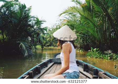 A young woman in a Vietnamese hat rides a boat on the Mekong River in Vietnam.The girl is traveling in a boat along the Mekong Delta in Vietnam.A serene river tour on the Mekong Delta, Can Tho Vietnam Royalty-Free Stock Photo #632121377