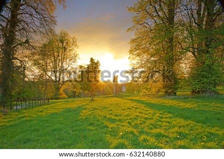 Sunset, with deliberate lens flare, over green fields and The Cotswolds in late Spring, Gloucestershire, England, UK #632140880