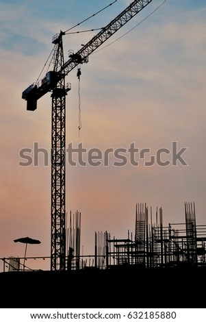 Real estate project by the control of civil engineering. Silhouette of construction site area and yellow crane in the evening with sunset in Bangkok, Thailand. #632185880