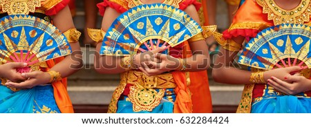 Asian travel background. Group of beautiful Balinese dancer women in traditional Sarong costumes with fans in hands dancing Legong dance. Arts, culture of Indonesian people, Bali island festivals. Royalty-Free Stock Photo #632284424