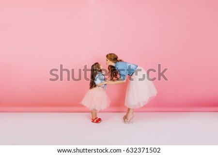 Full-length portrait of young slim mother and cute daughter in same attires posing on the pink background. Lovely young woman with long curly hair bent over to kiss her little birthday girl.