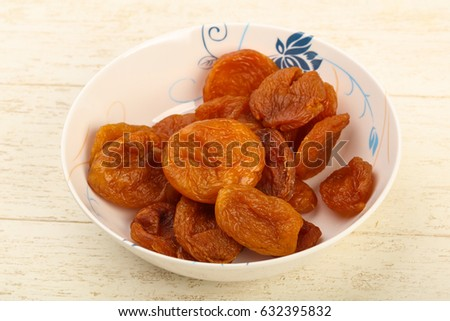 Dried apricots heap in the bowl over wooden background #632395832