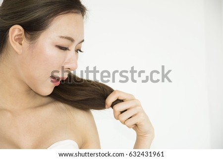 a beautiful woman catching hair and smile on white background. #632431961