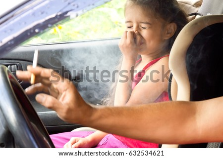 Stop smoking for children. Father smoking cigarette and the child choking of smoke in a car #632534621