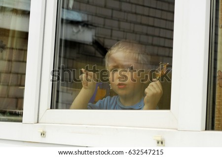 Cute little boy looking out through glass window at home, funny #632547215