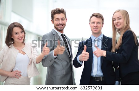 Business colleagues looking at camera and shoving thumbs up in t #632579801