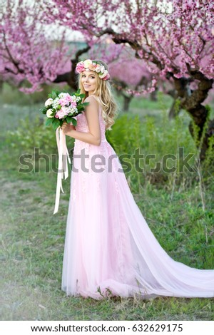 Young beautiful blonde woman in blooming garden. Bride. Woman in wreath and bouquet with ranunculus.  #632629175