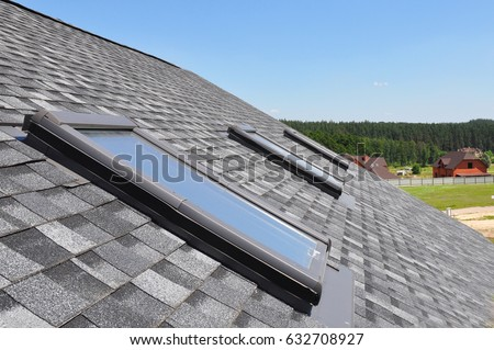 Attic skylight. Asphalt Shingles House Roofing Construction with Attic Roof windows, skylights waterproofing. #632708927
