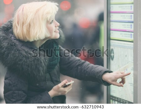 Young beautiful woman tourist using modern digital display board information, cute female watching movement of buses on electronic bulletin board in urban city #632710943