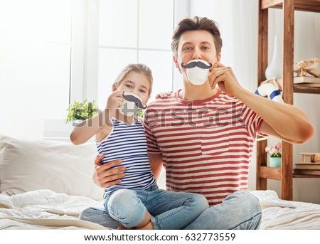 Happy father's day! Dad and his child daughter are playing and having fun together. Beautiful funny girl and daddy have mustaches on cups. Family holidays and togetherness. Royalty-Free Stock Photo #632773559