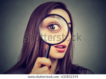 Curious woman looking through a magnifying glass  Royalty-Free Stock Photo #632832194