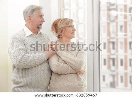 Cute elderly couple near window at home #632859467