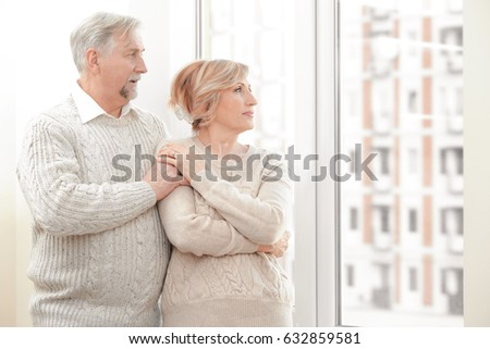 Cute elderly couple near window at home #632859581
