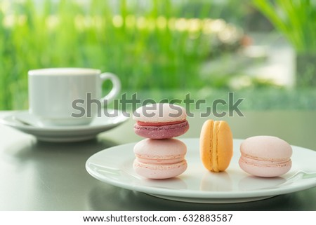 Good morning or Have a nice day message concept - white cup of frothy latte coffee with colourful French macaroons #632883587