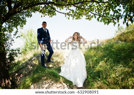 Happy wedding couple in love on sunny day stay near trees. #632908091