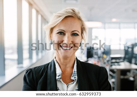 Close up portrait of successful mature businesswoman standing in office. Caucasian female executive in suit looking at camera and smiling. Royalty-Free Stock Photo #632959373